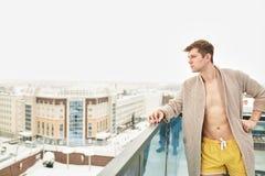 Jeune homme beau détendant sur la terrasse neigeuse d'hiver après l'obtention du bain bouillant photo stock