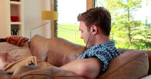 Jeune homme beau détendant sur son divan écoutant la musique banque de vidéos