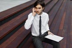 Jeune homme beau d'affaires à un appel téléphonique Photo libre de droits