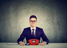 Jeune homme beau d'affaires s'asseyant au bureau avec la ligne téléphone de terre de vintage photos libres de droits