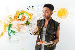 Jeune homme beau d'afro-américain tenant la palette et le pinceau image stock