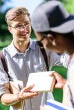 Jeune homme beau dans des lunettes tenant le livre et regardant le camarade de classe Photo stock