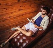 Jeune homme beau dans le costume blanc détendant sur le sofa de luxe avec le journal intime images stock