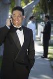 Jeune homme beau dans le smoking utilisant le téléphone portable chez Quinceanera Photos stock