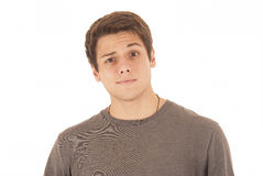 Jeune homme beau dans le tee-shirt gris avec l'augmenter de sourcil de visage d'amusement Photo stock