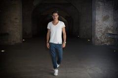 Jeune homme beau dans le vieux bâtiment marchant à l'intérieur de la galerie Images stock