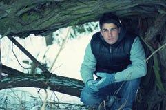 Jeune homme beau de acroupissement en hiver images stock