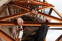 Jeune homme beau de hippie dans le chapeau tricoté dans la chemise de camouflage dans des lunettes de soleil posant la séance sur photos libres de droits
