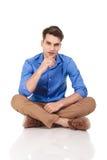 Jeune homme beau de mode s'asseyant avec ses jambes croisées Photographie stock libre de droits