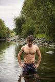 Jeune homme beau de muscle se tenant dans l'étang d'eau, nu Photo stock