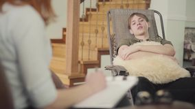 Jeune homme beau de portrait s'asseyant sur un berceau dans le bureau d'un psychologue, lui indiquant au sujet de son se tenir de banque de vidéos