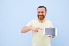 Jeune homme beau de sourire heureux avec une barbe montrant quelque chose sur un comprimé sur un fond bleu, lumineux et léger Photographie stock libre de droits