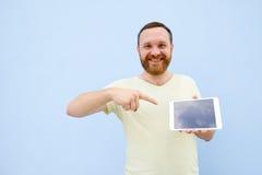 Jeune homme beau de sourire heureux avec une barbe montrant quelque chose sur un comprimé sur un fond bleu, lumineux et léger Photographie stock