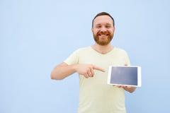 Jeune homme beau de sourire heureux avec une barbe montrant quelque chose sur un comprimé sur un fond bleu, lumineux et léger Photos stock