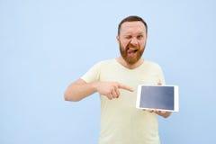 Jeune homme beau de sourire heureux avec une barbe montrant quelque chose sur un comprimé sur un fond bleu, lumineux et léger Photos libres de droits