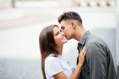 Jeune homme beau embrassant sa joue aimée du ` s dans la rue Photo libre de droits