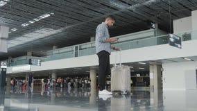 Jeune homme beau employant Smartphone et travaillant à l'aéroport tout en attendant sa file d'attente l'enregistrement, voyageant Photographie stock