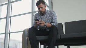 Jeune homme beau employant Smartphone et travaillant à l'aéroport tout en attendant sa file d'attente l'enregistrement, voyageant Photos stock