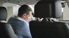 Jeune homme beau entrant dans la voiture et le sourire banque de vidéos