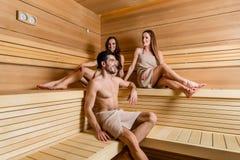Jeune homme beau et deux belles femmes s'asseyant dans un d moderne Photo libre de droits