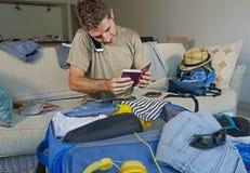 Jeune homme beau et heureux parlant avec l'ami au téléphone portable tenant les vêtements de organisation de valise de voyage d'e Photographie stock
