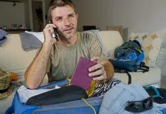Jeune homme beau et heureux parlant avec l'ami au téléphone portable tenant les vêtements de organisation de valise de voyage d'e Photos stock