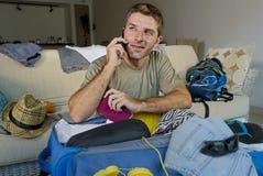 Jeune homme beau et heureux parlant avec l'ami au téléphone portable tenant les vêtements de organisation de valise de voyage d'e Photographie stock libre de droits