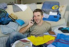 Jeune homme beau et heureux parlant avec l'ami au téléphone portable tout en emballant les vêtements de organisation et les chose Photo stock