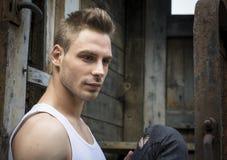 Jeune homme beau extérieur, avec les murs rouillés et vieux derrière Image stock