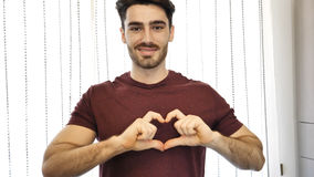 Jeune homme beau faisant le signe de coeur avec des mains Photo stock