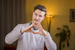Jeune homme beau faisant le signe de coeur avec ses mains Image libre de droits