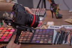 Jeune homme beau filmant son épisode visuel de blog au sujet de nouveaux produits cosmétiques Cosmétique de maquillage à la maiso photographie stock libre de droits