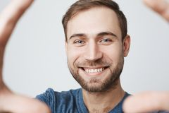 Jeune homme beau gai dans la chemise bleue avec les cheveux foncés souriant heureusement, recevant des actualités positives Type  photographie stock libre de droits