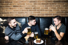 Jeune homme beau grillant avec de la bière et discutant tout en se reposant avec ses amis dans le bar de bière Photo stock