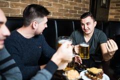 Jeune homme beau grillant avec de la bière et discutant tout en se reposant avec ses amis dans le bar de bière Photographie stock