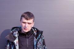 Jeune homme beau Le portrait d'un jeune homme, se tient sur un fond noir image stock