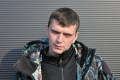 Jeune homme beau Le portrait d'un jeune homme, se tient sur un fond noir photographie stock