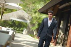 Jeune homme beau marchant en dehors du restaurant à travers la terrasse Photos stock
