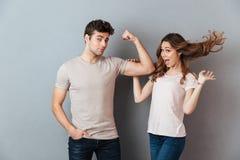 Jeune homme beau montrant le biceps à son amie stupéfaite Photo libre de droits