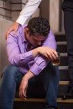 Jeune homme beau parlant à l'homme ivre s'asseyant sur des escaliers photo libre de droits