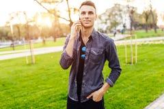 Jeune homme beau parlant au téléphone, marchant en parc images libres de droits