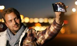 Jeune homme beau parlant du téléphone intelligent au coucher du soleil d'automne dans c Photo libre de droits