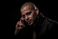 Jeune homme beau parlant du téléphone portable dans l'obscurité au transfe Images libres de droits