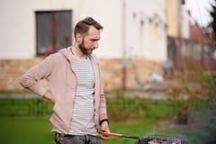 Jeune homme beau préparant le barbecue pour des amis dans l'arrière-cour Photo libre de droits