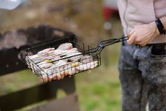 Jeune homme beau préparant le barbecue pour des amis dans l'arrière-cour Images libres de droits