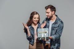 Jeune homme beau présent le boîte-cadeau à l'amie étonnée Image stock