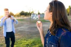 Jeune homme beau prenant la photo de son amie faisant des bulles de savon en parc Photos libres de droits