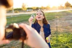Jeune homme beau prenant la photo de son amie faisant des bulles de savon en parc Photographie stock libre de droits