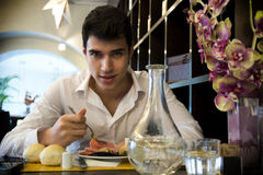 Jeune homme beau prenant le déjeuner dans le restaurant élégant Photo stock
