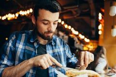 Jeune homme beau prenant le déjeuner dans seul le restaurant élégant Photographie stock